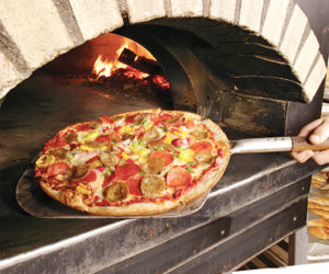 supreme pizza pulled from a wood fire oven