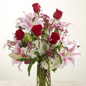 vase of roses and pink lillies