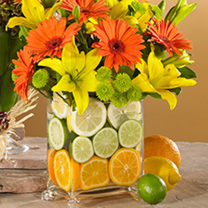 orange sunflowers with yellow lilies in a vase with lemons limes and oranges