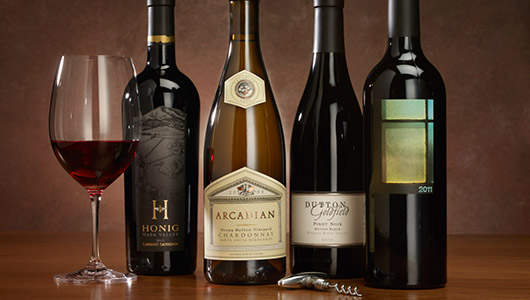 Four bottles of fine wine for the holidays lined up on a dark wood table
