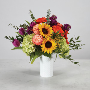 yellow sunflowers with green hydrangeas orange gerbera daisies and peach roses in a white hobnail vase