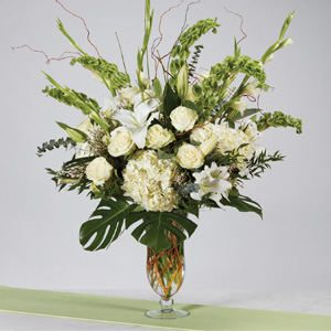 bouquet of assortment of white flowers and greenery in a tall clear glass vase
