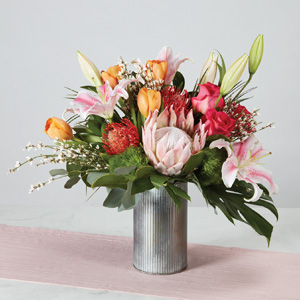 soft peach and pink roses pincushions and stargazer lilies in a silver metal galvanized vase