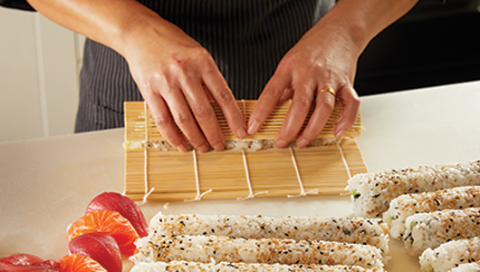 sushi chef rolling sushi roll